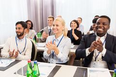 People applauding at business conference. Business and education concept - group of happy people applauding at international conference Royalty Free Stock Image