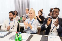 People applauding at business conference. Business and education concept - group of happy people applauding at international conference Stock Photos