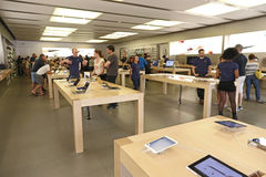 People in an apple store. With items displayed on tables Royalty Free Stock Photography