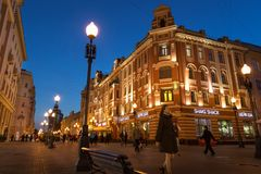People and architecture at Arbat walking street in Russia. Moscow, Russia - September 21, 2017: People and historical building decorated by warm light at Arbat Stock Photo