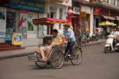 People in the area taking a cyclo ride in Hanoi,Vietnam. Stock Images