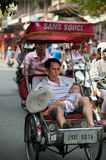 People in the area taking a cyclo ride in Hanoi,Vietnam. Stock Photos