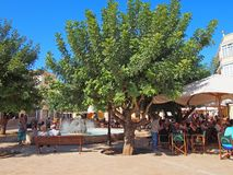 People around the fountain in Placa d`Artruix Ciutadella, the old capital of Menorca, Spain with surrounding cafes royalty free stock photo