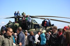 People around and on russian attack helicopter Mi-24 on airshow in sunny day. Time of the airshow on Pushkin airdrome June 4, 2017. Saint-Petersburg, Russia stock photography