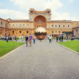 People around Sphere within sphere in Courtyard of the Pinecone. VATICAN: People around Sphere within sphere in Courtyard of the Pinecone at Vatican Museums Royalty Free Stock Image
