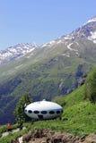People around UFO that landing between mountains Stock Image