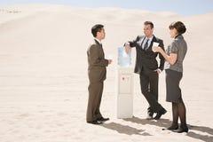 People around water cooler in the desert Stock Photo