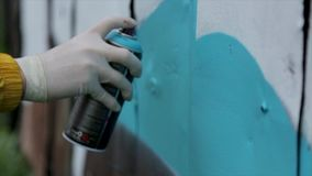 People, art, creativity and youth culture concept - close up of hand drawing graffiti with spray paint on street wall stock footage