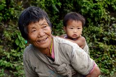 People of Arunachal Pradesh. An old woman carrying her grandchild in the village of Arunachal Pradesh Royalty Free Stock Photos