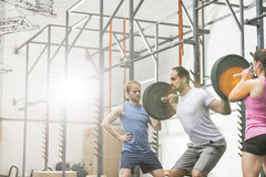 People assisting man in lifting barbell at crossfit gym Stock Photography