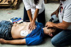 People assisting an unconscious man. People assisting an unconscious men after cardiac arrest with defibrillator Royalty Free Stock Images