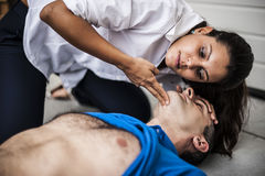 People assisting an unconscious man. People assisting an unconscious men after fatal accident with cardiopulmonary resuscitation and defibrillator Stock Image