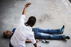 People assisting an unconscious man. People assisting an unconscious men after fatal accident with cardiopulmonary resuscitation and defibrillator Stock Photos
