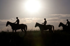 People astride horses. Against a rising sun, it is tinted Stock Photo