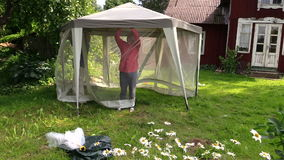 People attach protective tent bower net in garden house yard stock video footage