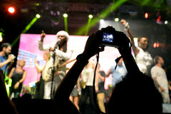 People from the audience recording and taking pictures with their cameras at Chic featuring Nile Rodgers royalty free stock photography