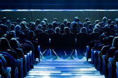 People in the auditorium looking at the stage. Shooting from the back Royalty Free Stock Photo
