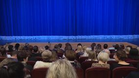 People in the auditorium of the theater before the performance or in the intermission. Blue curtain on stage stock video footage