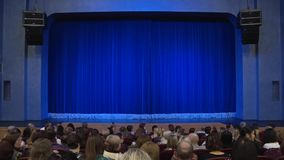 People in the auditorium of the theater before the performance or in the intermission. Blue curtain on stage stock video