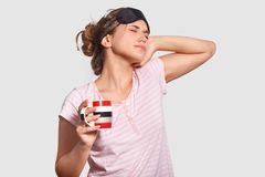 People and awakening concept. Sleepy young European female wears eye mask on head, pyjamas, stretches after getting up early, drin. Ks hot coffee, cant open eyes stock image