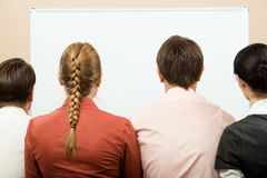 People backs. Rear view of business team with whiteboard in front of them royalty free stock images