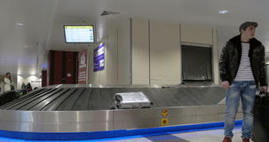 People in baggage claim area of airport. ROME, ITALY - FEBRUARY 8, 2015: Arrived people with travel bags passing by the luggage conveyor belt at the airport stock video footage