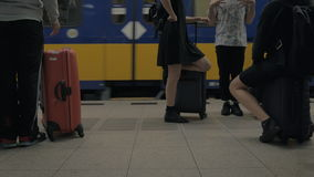 People with baggage waiting for the train at railway station. AMSTERDAM, NETHERLANDS - AUGUST 04, 2016: People with luggage waiting on the platform and train stock video footage