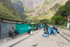 People and baggages on railway track to Machu Picchu, Peru. Hydroelectric Station, Peru - September 8, 2015: Food stalls, peruvian people and tourists at Stock Photography