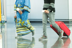 People with bags and suitcases in airport. Or station. Female and male legs in sport shoes walking on grey tile floor. Hands holding passports and tickets Stock Images