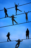 People Balancing on Tight Wire Royalty Free Stock Image