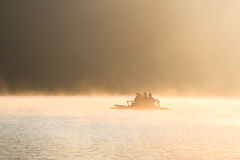 People on bamboo rafting on a lake at sunrise Royalty Free Stock Photography