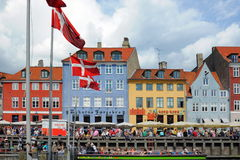 People on bank in Copenhagen, Denmark. Copenhagen view with flags of Denmark over the typical danish colorful houses and a lot of people - crowd sitting on the Royalty Free Stock Photography