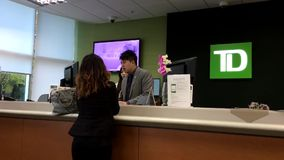 People at a bank counter talking to the teller