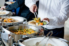 People at a banquet. Men in blue suits choosing food at a banquet stock images