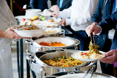 People at a banquet. Men in blue suits choosing food at a banquet stock image