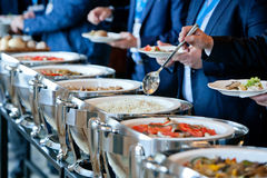 People at a banquet. Men in blue suits choosing food at a banquet stock photography