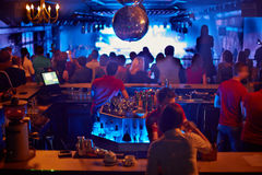 People in bar look at musical show royalty free stock image