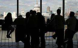 People in Bar Looking at London. People at bar overlooking the Thames with view of St Pauls cathedral in London, England royalty free stock image