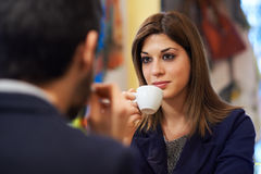 People in bar with woman drinking espresso coffee Royalty Free Stock Image