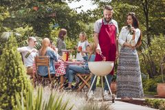 People during barbeque in backyard. A couple standing by a grill, the men turning around a sausage, the women with a beer bottle in her hand, with other people stock photos
