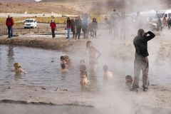 People bathe in geyser thermal water, Chile. Stock Images