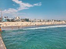 People bathe and sunbathe on the beach. View from Venice Beach Pier, Los Angeles, California, USA.  Stock Photos