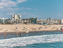 People bathe and sunbathe on the beach. View from Venice Beach Pier, Los Angeles, California, USA.  Royalty Free Stock Image