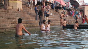 People bathing on the ghats of Ganges river in Varanasi. VARANASI, INDIA - 22 FEBRUARY 2015: People bathing on the ghats of Ganges river in Varanasi stock video