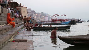 People bathing on the ghats of Ganges river in Varanasi. VARANASI, INDIA - 22 FEBRUARY 2015: People bathing by the ghats of Ganges river in Varanasi stock video footage