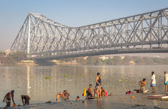 People bathing at the Hooghly river banks with the historic Howrah bridge at the backdrop. Stock Images