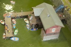 People bathing on a pontoon with boats in a miniature world setup. People bathing, relaxing, enjoying summer on the lake shore with boats, miniature world Stock Photo