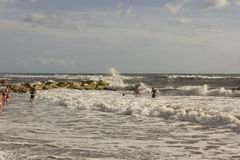 People bathing in rough seas near the rock Royalty Free Stock Photos