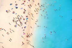 People bathing in the sun, swiming and playing games on the beac. H. Tourists on the sand beach of Navagio Zakynthos Greece Royalty Free Stock Photography