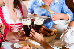 People in Bavarian Tracht eating in restaurant or pub. Young people in traditional Bavarian Tracht eating with sausages in restaurant or pub lunch or dinner Stock Image